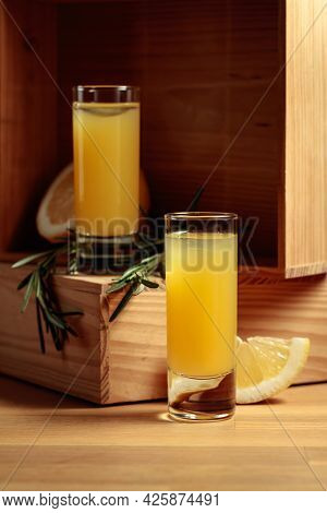 Traditional Homemade Lemon Liqueur Limoncello And Fresh Citrus And Rosemary.