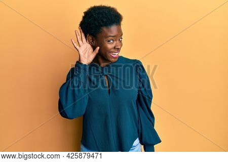 Young african american girl wearing casual clothes smiling with hand over ear listening an hearing to rumor or gossip. deafness concept.