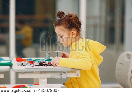 Little Girl Child With Constructor Checking Technical Toy. Children Robotics Constructor Assemble Ro