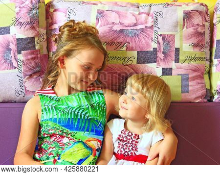 Little Girls Look At Each Other. Portrait Of Two Sisters. Sisterhood. Happy Children. Older And Youn