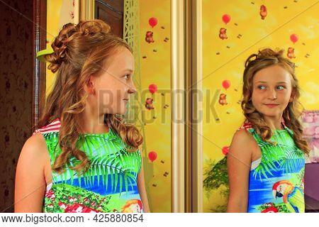 Girl With Lush Hairstyle Poses In Front Of Mirror. Portrait Of Girl In Front Of Mirror. Smart Child.