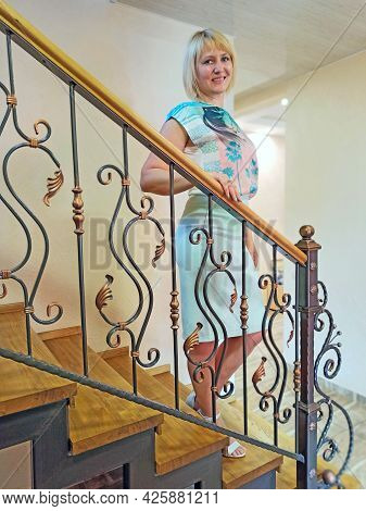 Portrait Of Stylish Woman Standing On Stairs With Beautiful Railing. Hostess Of House With Balustrad