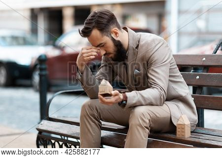 Eviction From Home. Upset Man Sits On A Bench Outside With A Miniature House. Loss Of Housing During