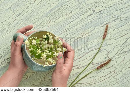 Old Porcelain Cup In Hands With Pale Yellow Wild Flowers. Aged Crackled Paint, Flat Lay On Textured