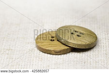 Two Wooden Buttons Lie On Burlap, Side View, Close-up