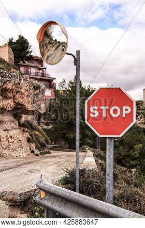 Stop Sign And Mirror Panel On Mountain Road In A Cloudy Day. Road Surrounded By Vegetation.