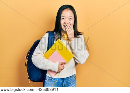 Young chinese girl holding student backpack and books laughing and embarrassed giggle covering mouth with hands, gossip and scandal concept