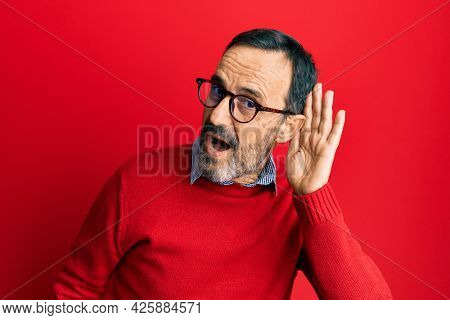 Middle age hispanic man wearing casual clothes and glasses smiling with hand over ear listening an hearing to rumor or gossip. deafness concept.