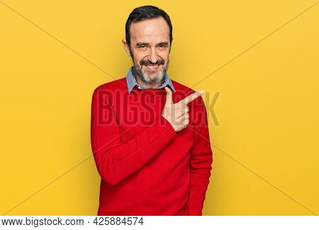 Middle age hispanic man wearing casual clothes cheerful with a smile of face pointing with hand and finger up to the side with happy and natural expression on face