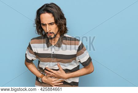 Young hispanic man wearing casual clothes with hand on stomach because indigestion, painful illness feeling unwell. ache concept.
