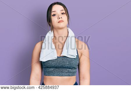 Young hispanic girl wearing sportswear and towel looking sleepy and tired, exhausted for fatigue and hangover, lazy eyes in the morning.