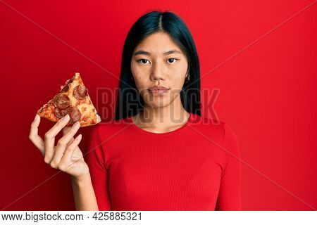 Young chinese woman holding italian pizza thinking attitude and sober expression looking self confident