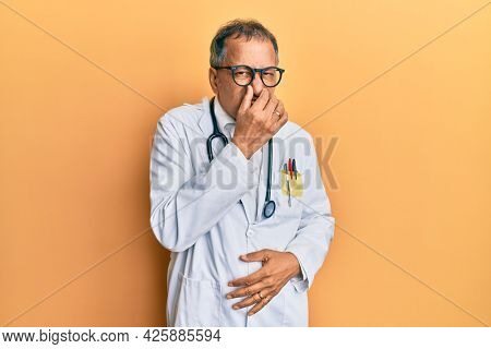 Middle age indian man wearing doctor coat and stethoscope smelling something stinky and disgusting, intolerable smell, holding breath with fingers on nose. bad smell