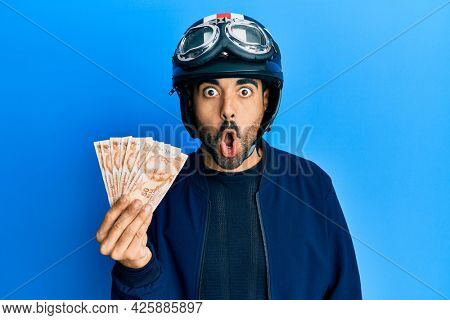 Young hispanic man wearing motorcycle helmet holding turkish lira scared and amazed with open mouth for surprise, disbelief face