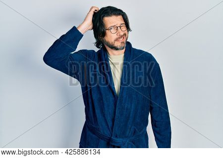 Middle age caucasian man wearing bathrobe and glasses confuse and wonder about question. uncertain with doubt, thinking with hand on head. pensive concept.