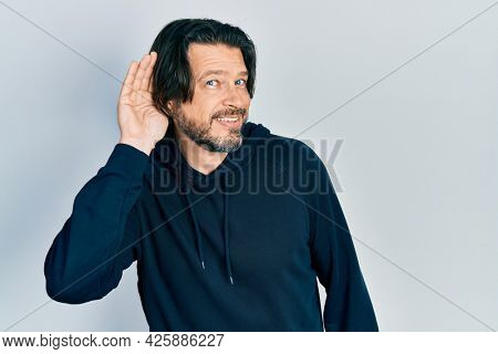 Middle age caucasian man wearing casual sweatshirt smiling with hand over ear listening an hearing to rumor or gossip. deafness concept.