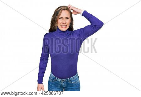 Young blonde woman wearing casual clothes confuse and wonder about question. uncertain with doubt, thinking with hand on head. pensive concept.
