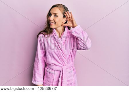 Young blonde woman wearing bathrobe smiling with hand over ear listening an hearing to rumor or gossip. deafness concept.