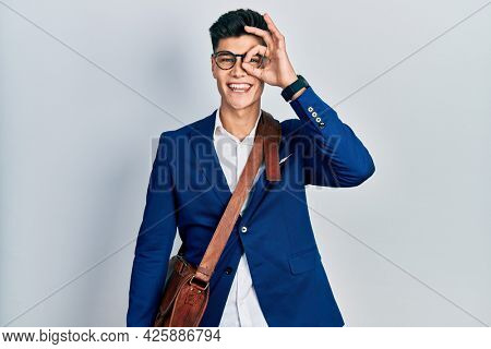 Young hispanic man wearing business clothes doing ok gesture with hand smiling, eye looking through fingers with happy face.