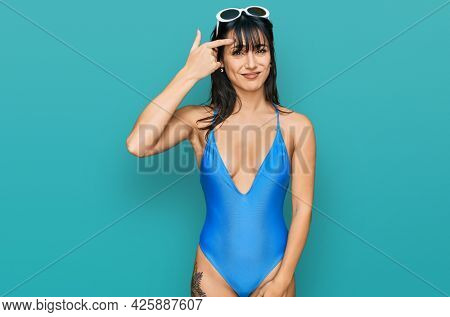 Young hispanic woman wearing swimsuit and sunglasses pointing unhappy to pimple on forehead, ugly infection of blackhead. acne and skin problem