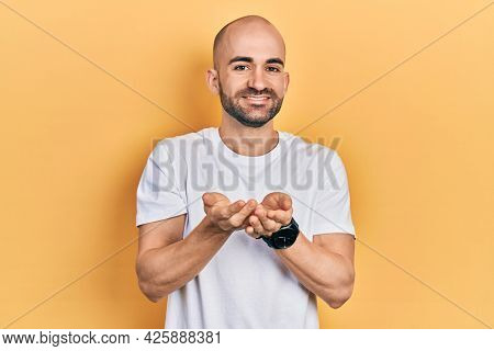 Young bald man wearing casual white t shirt smiling with hands palms together receiving or giving gesture. hold and protection