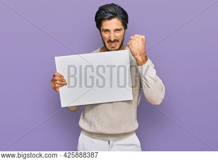 Young hispanic man holding blank empty banner annoyed and frustrated shouting with anger, yelling crazy with anger and hand raised