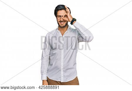 Young hispanic man wearing business shirt and glasses doing ok gesture with hand smiling, eye looking through fingers with happy face.