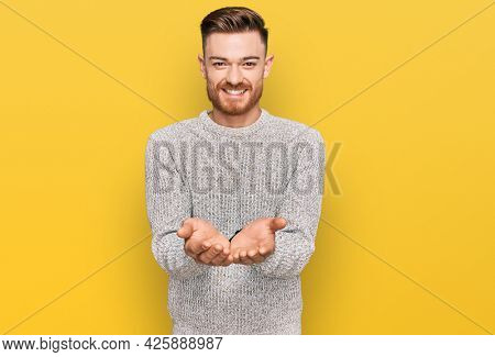 Young redhead man wearing casual winter sweater smiling with hands palms together receiving or giving gesture. hold and protection