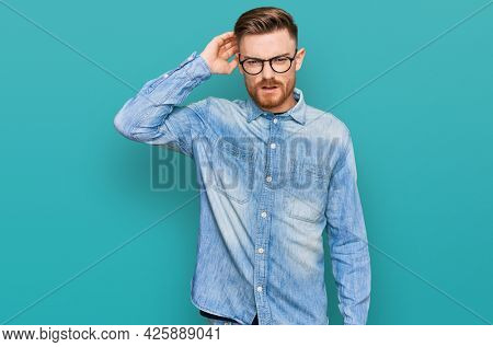 Young redhead man wearing casual denim shirt confuse and wonder about question. uncertain with doubt, thinking with hand on head. pensive concept.