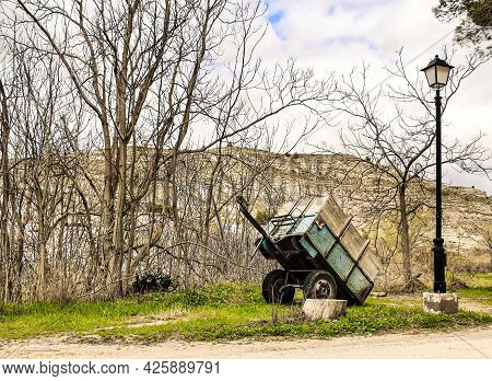 Trailer Abandoned In The Countryside And Next To A Streetlight Among Vegetation. Mountain In The Bac