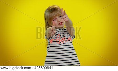 Little Blonde Teen Kid Child Girl In T-shirt Pointing Around With Finger Gun Gesture, Looking Confid