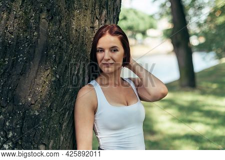 A Girl With A Bob Hairstyle Caucasian Walks In A City Park.