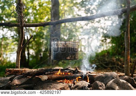 A Tourist Soot-covered Bowler Hat Hangs Over A Smoking Campfire At A Forest Camp In Summer. Camping