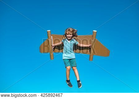 Dreams Of Travel. Child Flying On Jetpack With Toy Airplane On Sky Background. Happy Child Boy Playi