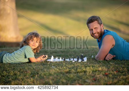 Father And Son Playing Chess Lying On Grass At Lawn Park. Fathers Day, Love Family, Parenthood, Chil