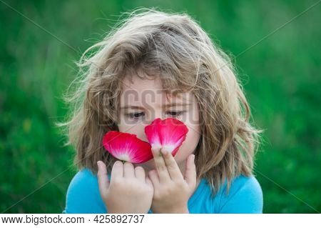 Close-up Portrait Of Cheerful Child Smelling Flowers. Cute Joyful Little Boy Kid. Close Up Portrait