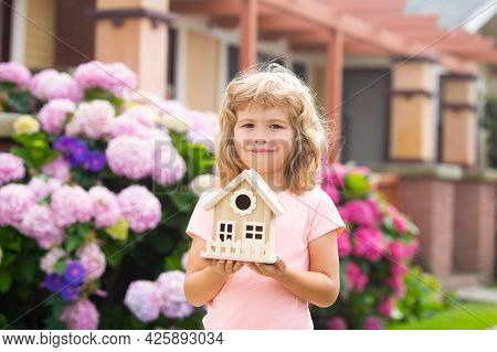 Design Of Your Dream House. Kid Playing With Small House Model Outdoors At Home Garden.