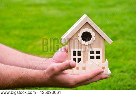 House In Caring Male Hands. Hand Holding Toy House Close Up. Small Miniature Toy House. Mortgage Pro