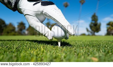 Hand In Golf Gloves Putting Golf Ball On Tee In Golf Course. Golf Ball Is On Tee On Green Grass Back