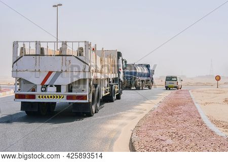 Group Of Lorry Transports, Delivery Truck And Tanker, On Highway Through The Desert With Blurred San