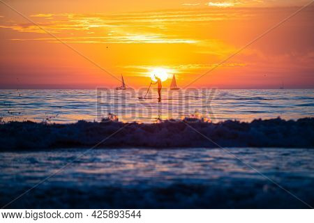 Man Paddle Boarding During A Beautiful Sunrise. Sunset At The Sea. Sunrise At Beach. Colorful Ocean
