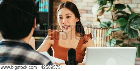 Cheerful Young Asian Female Podcaster Holding A Questionnaire While Interviewing Male Guest At Works