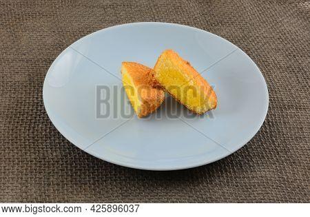 Custard Cream Cake Halves On Blue Snack Plate On Gray Burlap