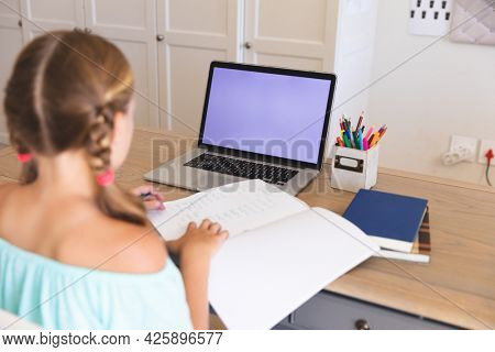 Caucasian girl having video call during class on laptop with copy space, sitting at desk at home. online schooling, distance learning and education at home.
