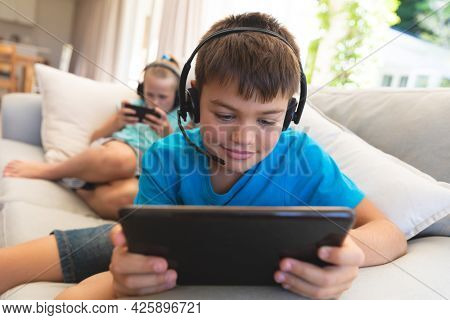 Caucasian brother and sister wearing headphones and using tablets at home. childhood with technology, spending free time at home.
