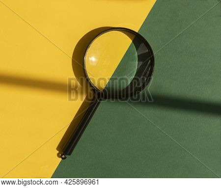 Magnifying Glass Over Yellow And Green Background With Beautiful Daylight, Top View.
