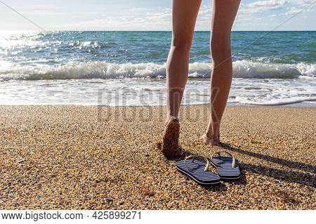 Female Legs And Flip-flops Against Sea Landscape In Summer Evening At Sunset. Beautiful Woman Walkin