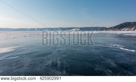 Cracks And Some Snow Are Visible On The Smooth Ice Of The Frozen Lake. In The Distance, A Mountain R