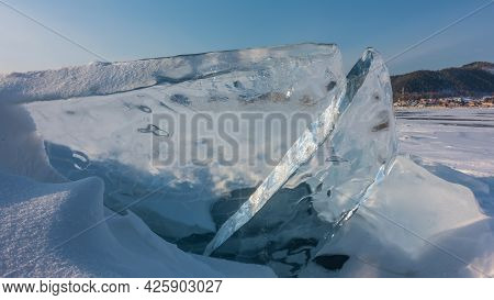 Transparent Ice Floes On The Frozen Lake Against The Blue Sky. Close-up. Glare Of The Sun On Sharp E