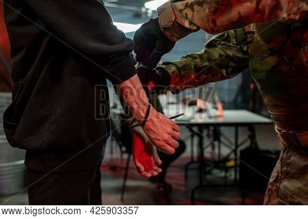 Officer in military outfit putting cuffs on hands of captured criminal